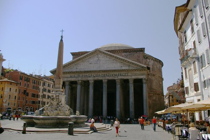 This photo shows an exterior view of the Pantheon as it stands today. The building is circular with a portico of large granite Corinthian columns under a pediment.