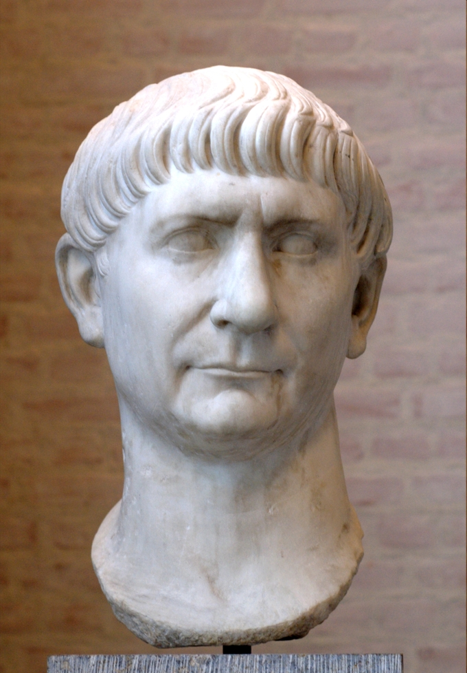 This photo shows a bust of Trajan. He has a full head of hair with bangs that stop above his eyebrows, triangular nose, and thin straight lips.