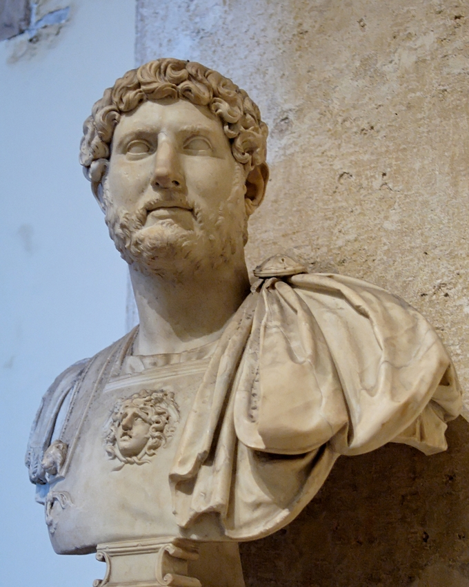 This photo shows a bust of Hadrian. He has curly hair and a beard.