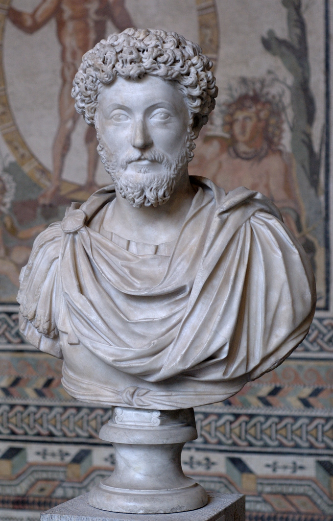 This is a photo of a bust of Marcus Aurelius. He has curly hair and long, curly beard.