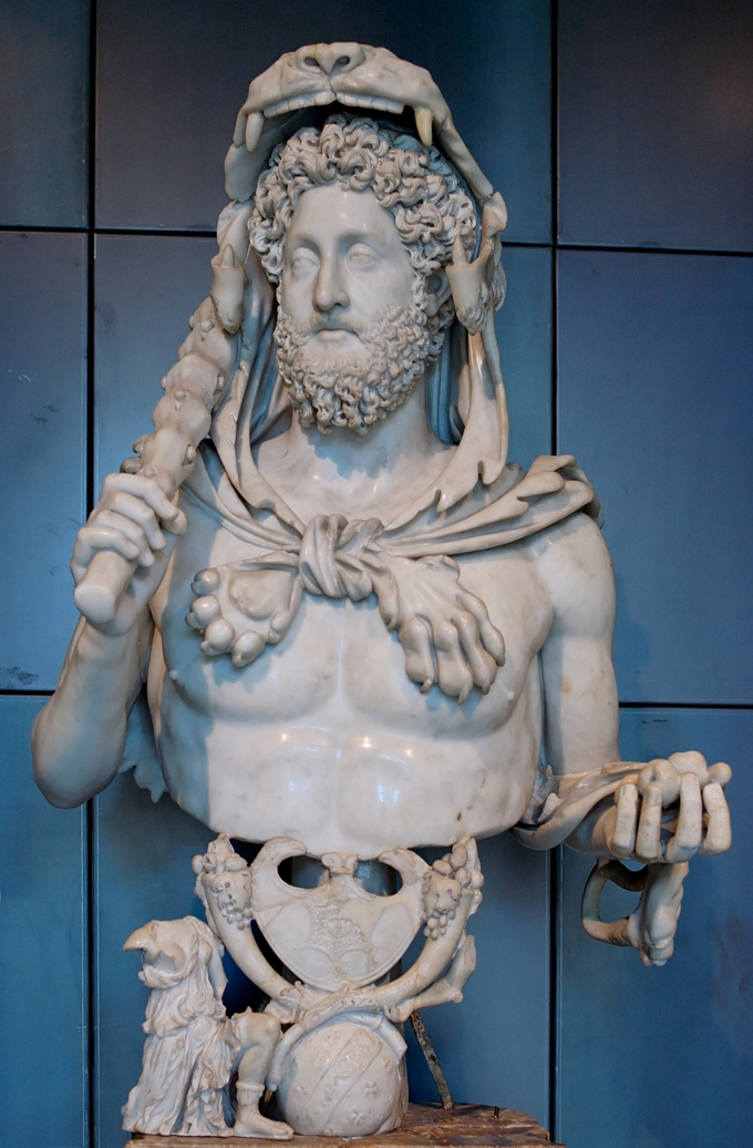 This photo shows a statue of Commodus as Hercules. Here, the Roman Emperor has taken on the guise of the mythological hero, Hercules. He has been given the attributes of the hero: a lion skin placed over his head, a club placed in his right hand, and the golden apples of Hesperides in his left.