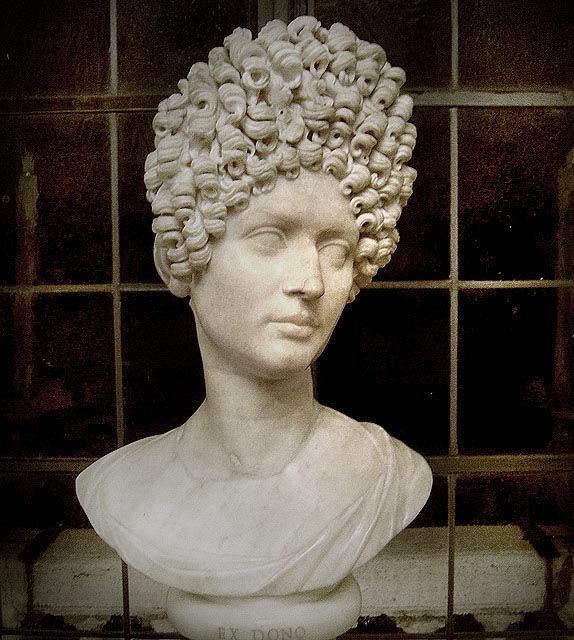 This is photo of a bust of a Flavian woman. It shows a fashionable Flavian hairstyle, a stack a tight curls arranged at the crown.