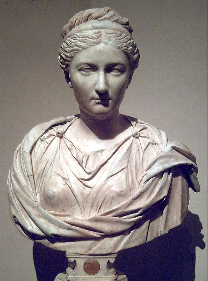 This photo shows a bust of Vibia Sabina wearing her hair in a braided updo, a Greek hairstyle.