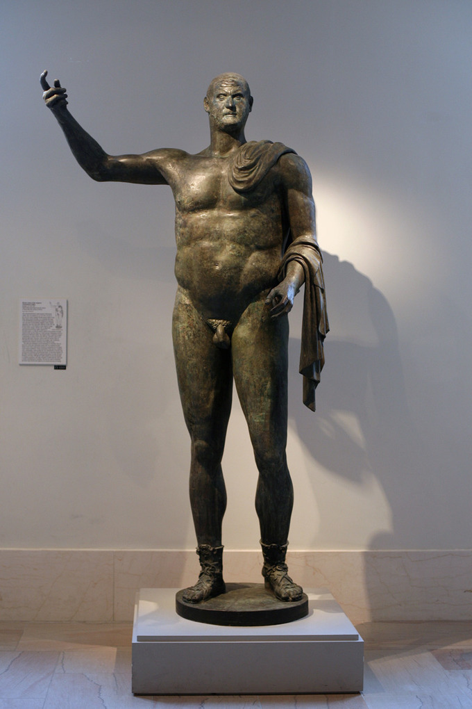 This is a photo of the statue of Trebonianus Gallus. It is a full-length standing nude statue. The body is large, bulky, and muscular. The head is disproportionately small.
