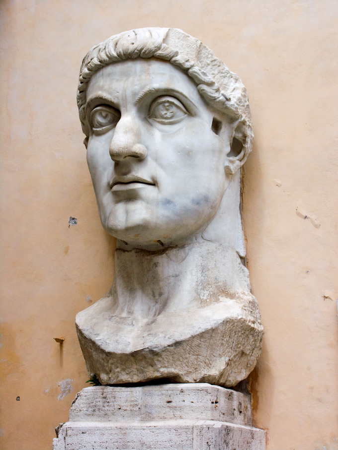 Photo of the giant sculpture of the head of the colossus of Constantine, depicted with large wide eyes and a strong jawline.
