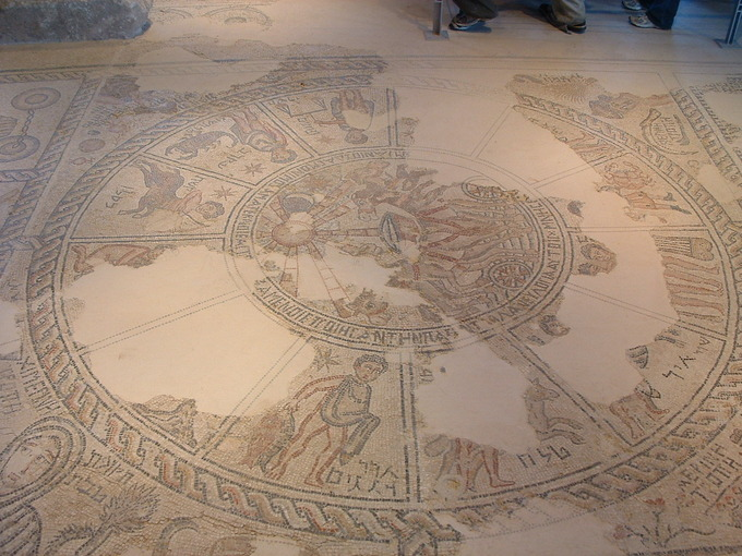 This is a photo of a mosaic on the floor at the Sepphoris synagogue. There is a large Zodiac with the names of the months written in Hebrew. Helios sits in the middle, in his sun chariot.