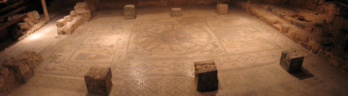 This is a panoramic photo of the nave mosaics in Beth Alva. It shows three panels. The left panel depicts the binding of Isaac. The center panel depicts a zodiak circle. The right panel depicts a synagogue scene.