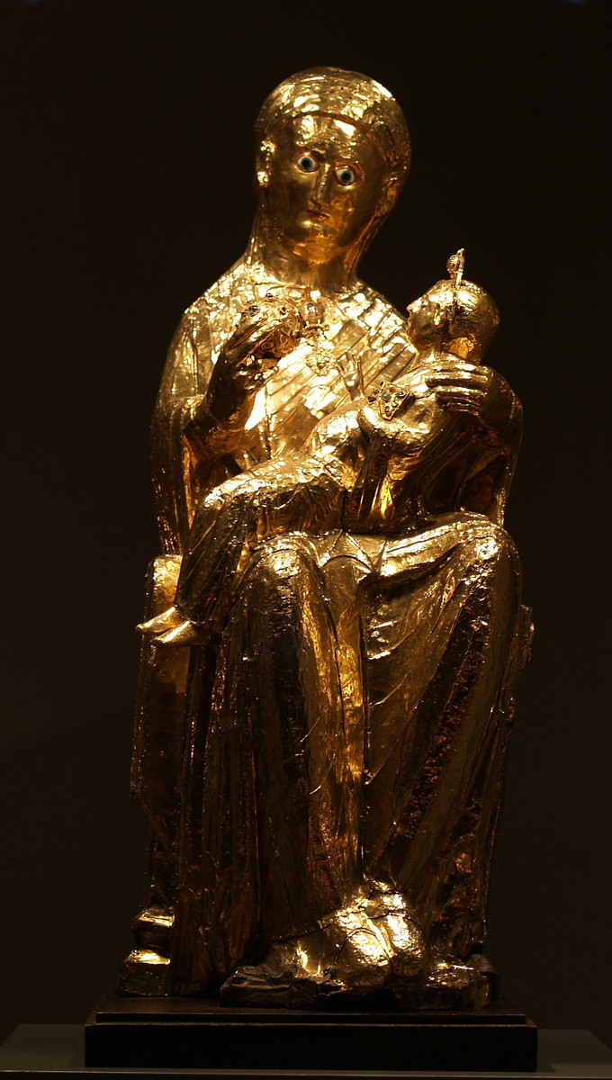 This is photo of the Golden Madonna of Essen, a sculpture of the Virgin Mary and the infant Jesus. Mary is depicted sitting on a stool, with a slightly oversized Christ child figure sitting on her lap. She wears a robe and veil. In her right hand she holds a globe with her thumb and two fingers, while her left hand supports the infant in her lap.