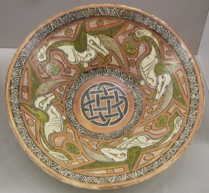 This photo shows a 10th century dish painted with complex geometric patterns and a repeated bird portrait. Islamic art has very notable achievements in ceramics, both in pottery and tiles for walls, which reached heights unmatched by other cultures. This dish is from East Persia or Central Asia.