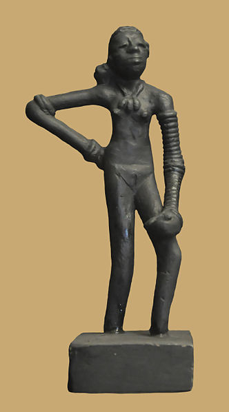 This is a photo of the Dancing Girl of Mohenjo-daro. Full-length statuette of a nude female figure with long, lean legs and stylized facial features. She wears a stack of bracelets and a large necklace.