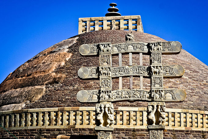 This is a current-day photo of the Stupa at Sanchi, India, illustrating the mound-like or hemispherical structure of stupas. It is decorated with ornated gold metalwork.