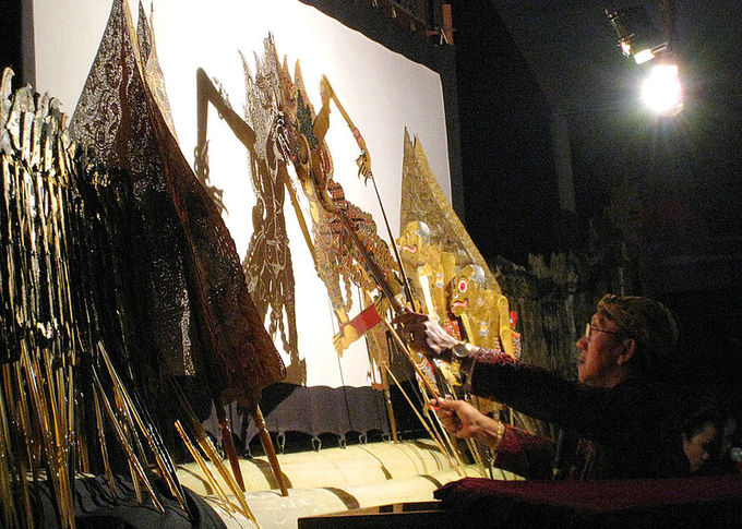 This current-day photo shows a backstage view of a wayang performance. The wayang kulit performance by the famous Indonesian dalang (puppet master) Ki Manteb Sudharsono, with the story Gathutkaca Winisuda.