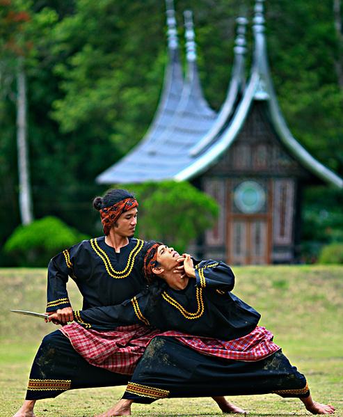 This is a current-day photo of two men practicing Silat Minangkabaut, a particular form of silat, outdoors.