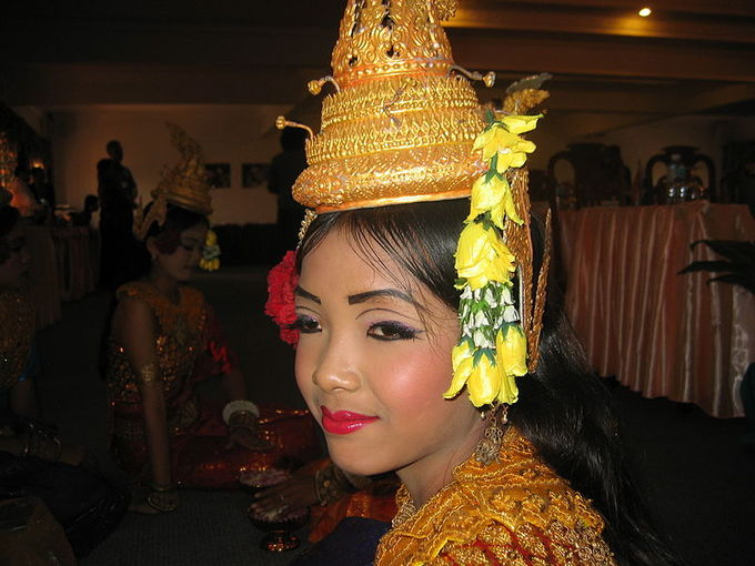This is a current-day photo of a female Khmer dancer in Siem Reap in profile view. She wears a yellow hat and dramatic eye and lip makeup.