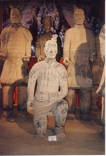 Photo of four figures from the Terracotta Army. Three are standing up straight and one kneels on one knee in front of them.