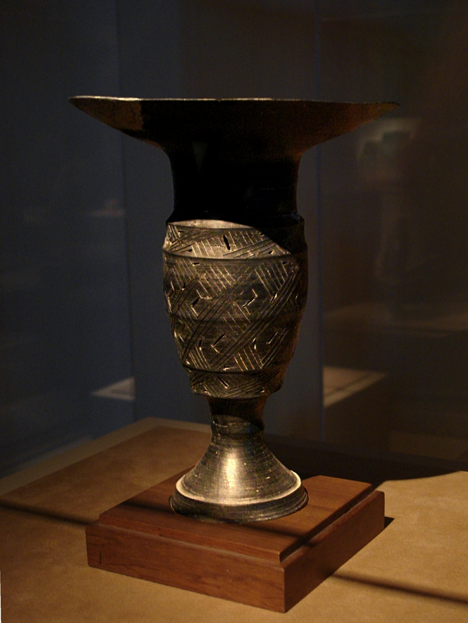 A vase, partially hidden in shadow, with decorative, weaving lines.