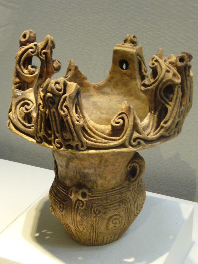 "A vessel with an elaborately decorated base and an ""open,"" crown-like top that is also elaborately decorated."