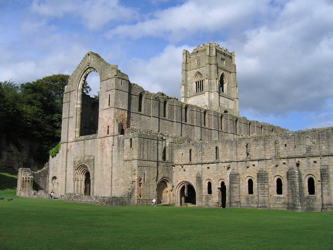 Image of Fountains Abbey, a large, stone building with very little decoration with a green lawn in the foreground.