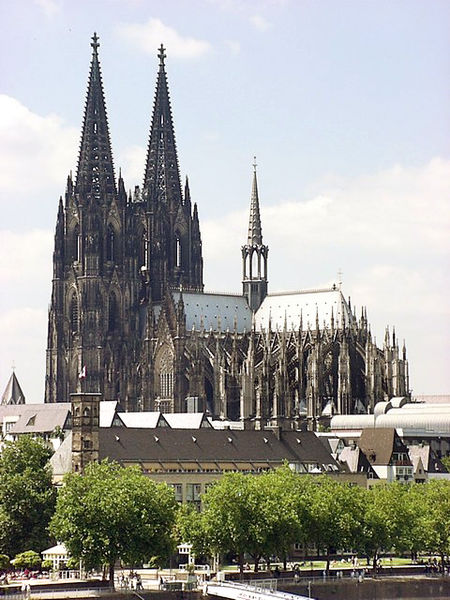 External image of the cathedral. The building is dominated by its huge spires. Externally the outward thrust of the vault is taken up by flying buttresses in the French manner.
