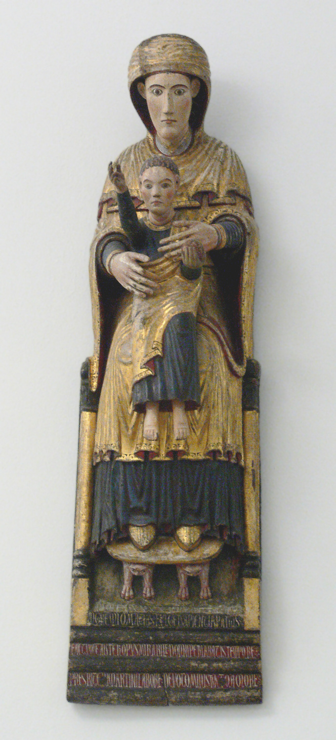 Sculpture of Mary seated on a throne holding the Holy Child in her lap. The figures are dressed in blue and gold and the Holy Child holds out his right arm.