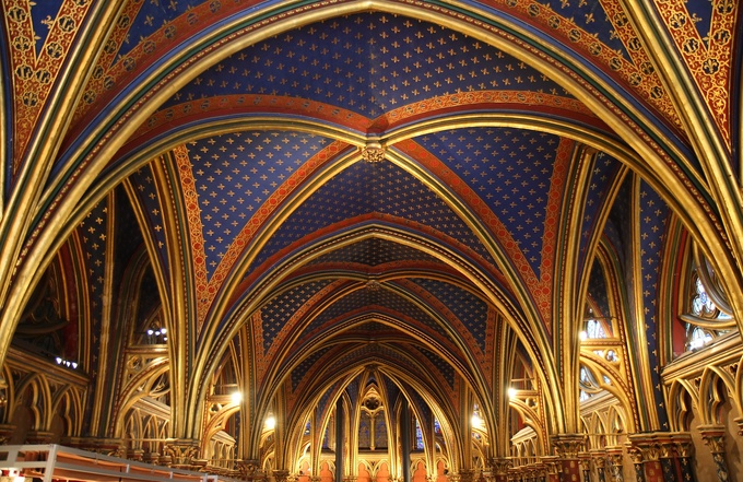 The ceiling is richly colored and decorated. The prominent design is gold fleur de lys on a blue background.