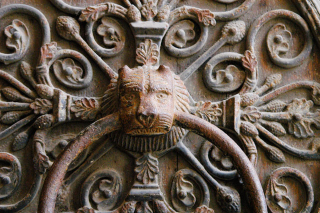 Close up of elaborate door knocker featuring a lion's head.