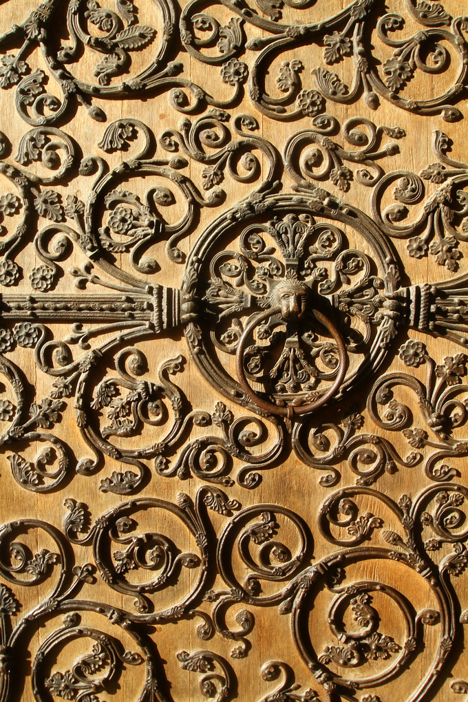 Image of an elaborately decorated door, featuring a lion's head door knocker in the center.