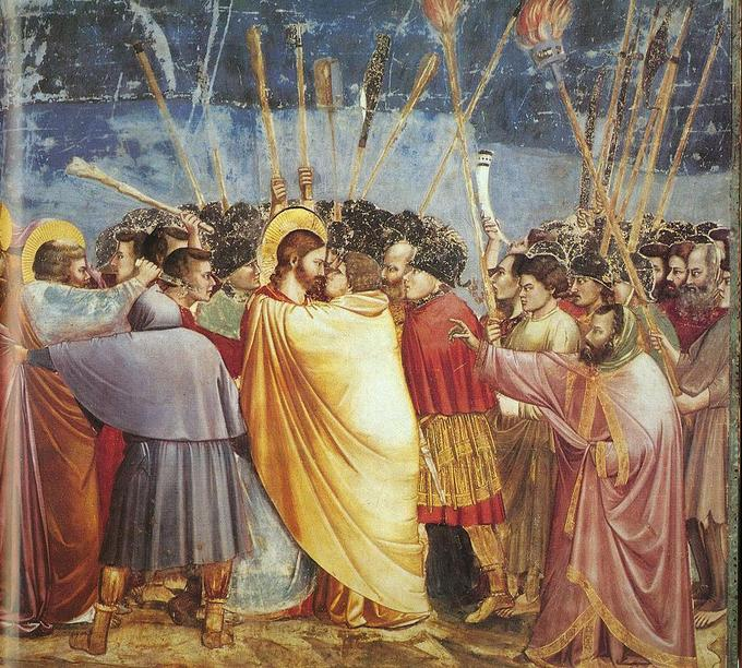 Judas is shown kissing Jesus in the center with many men around them in motion.