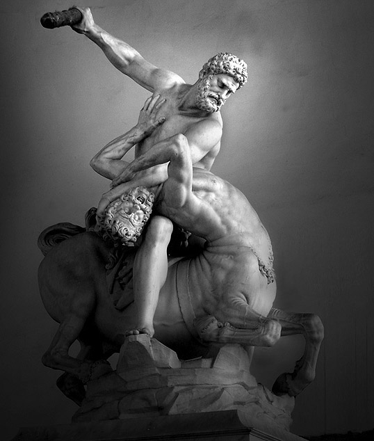 Sculpture depicts Hercules on top of the centaur Nessus, holding the centaur's head down. Hercules extends his right arm back, holding an object that he is using to beat Nessus.