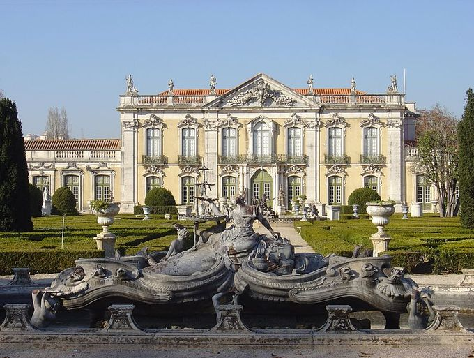 Palace is pictured with an elaborate fountain in the foreground.