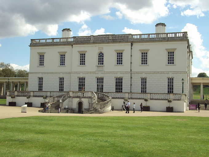 Picture of the Queen's House with a green yard in the foreground. The white house is a simple, symmetrical box design.