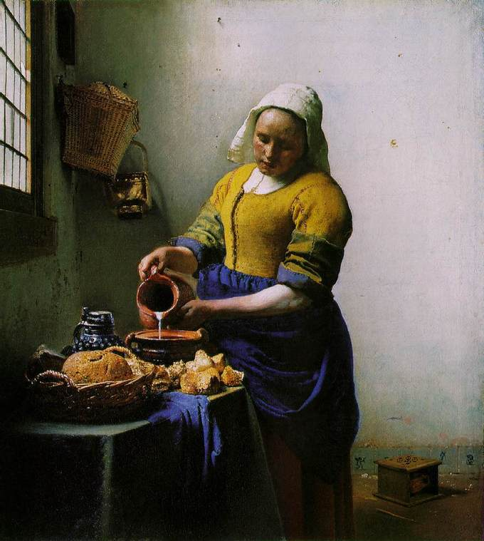 A maid or servant is seen in a plain room carefully pouring milk into a squat earthenware container on a table. Also on the table are various types of bread. She is a young, sturdily built woman wearing a crisp linen cap, a blue apron and work sleeves pushed up from thick forearms. A foot warmer is on the floor behind her. Intense light streams from the window on the left side of the canvas.