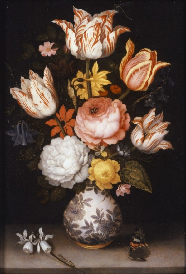 A variety of flowers in different colors are in a vase decorated with a floral design. One flower has fallen on the table, and a butterfly sits on the other side of the table.