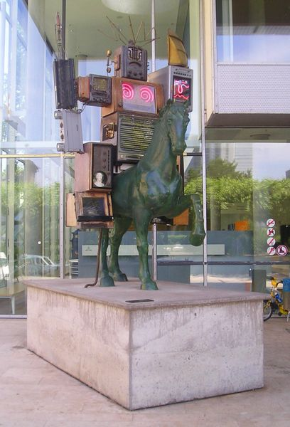 A boxy robot rides a green horse.