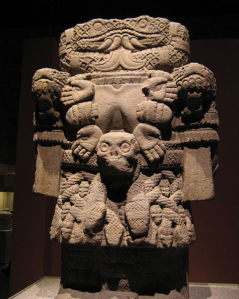 A boxy statue with a necklace made of hands and a skirt made of snakes.
