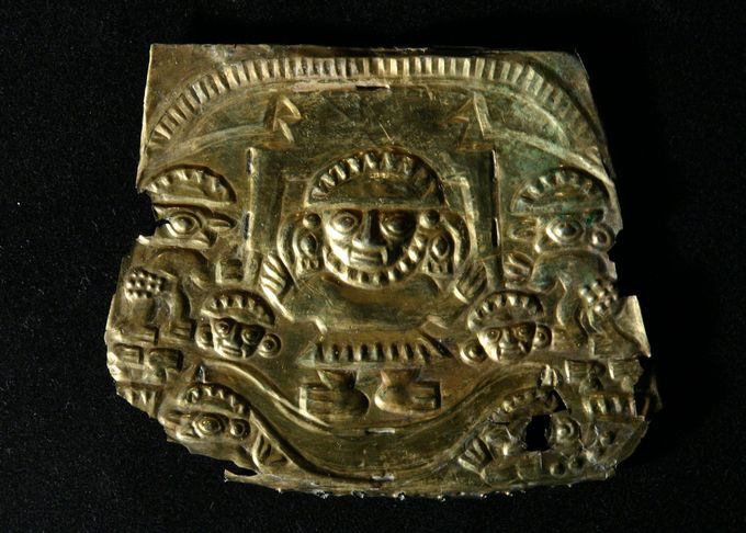 Metal plaque depicting a figure in the center with smaller figures on the edges.