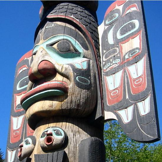 This totem pole depicts a giant head painted in various colors.