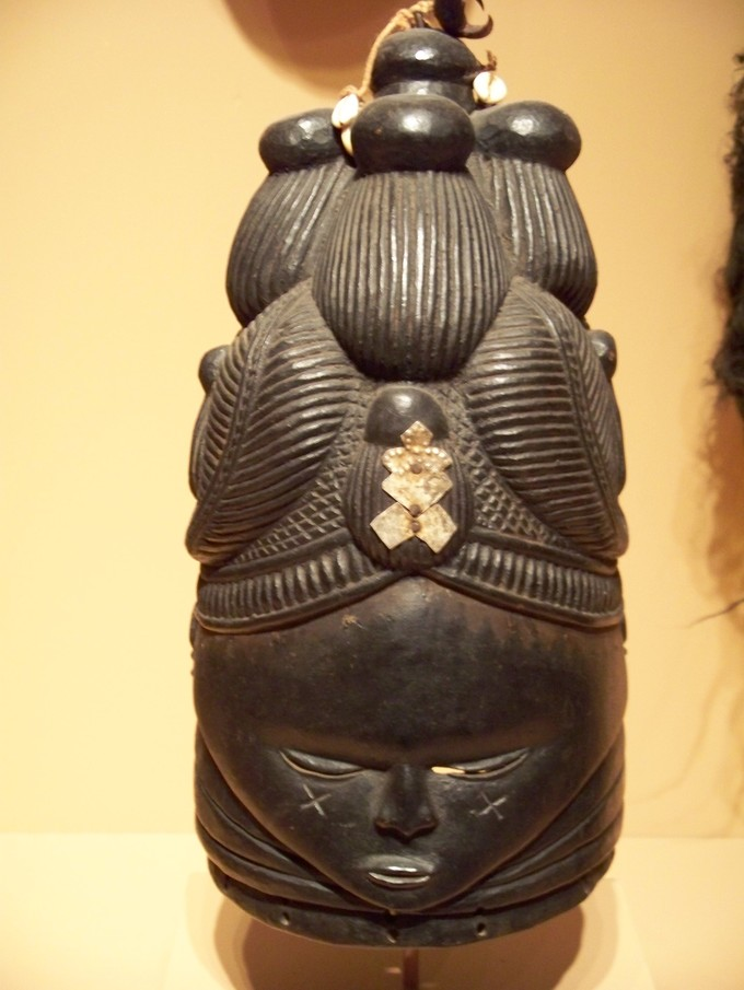 This mask has a face with a intricately carved headdress or hair.
