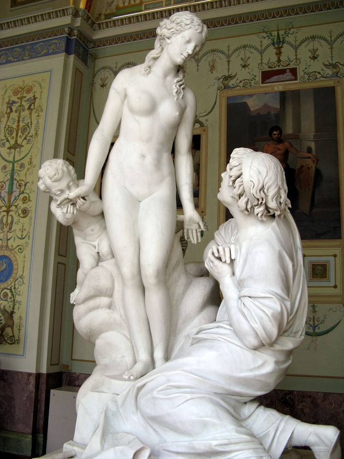 Sculpture depicts Pygmalion on his knees, falling in love with a sculpture of a woman. A cherub kisses the hand of the woman.