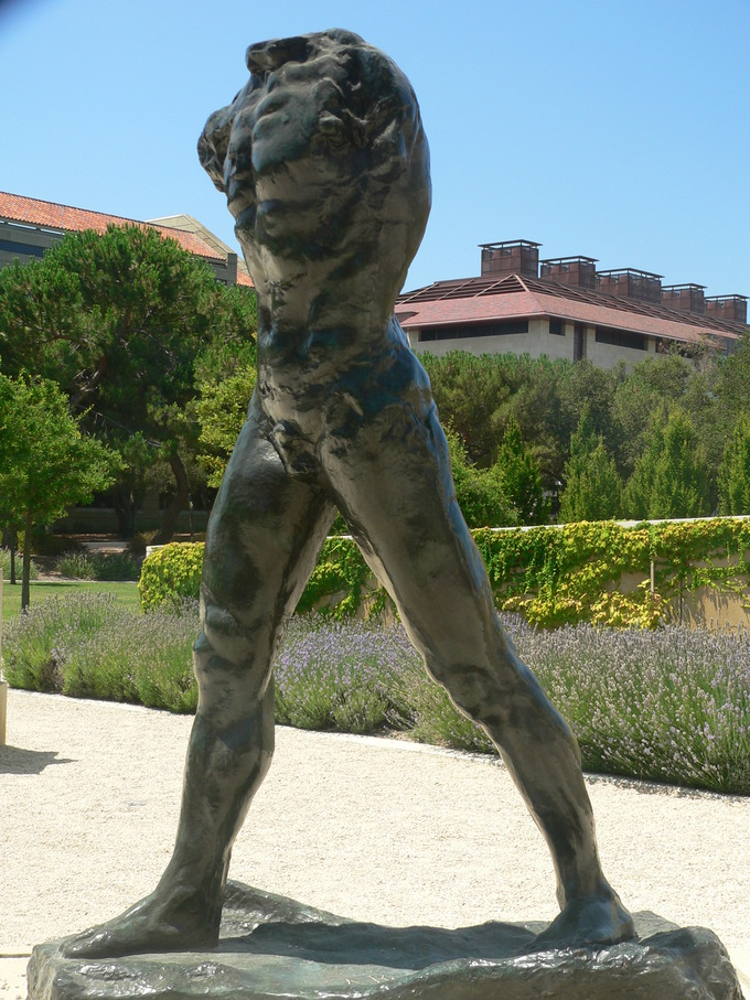 The statue is a nude male walking with no arms and no head.