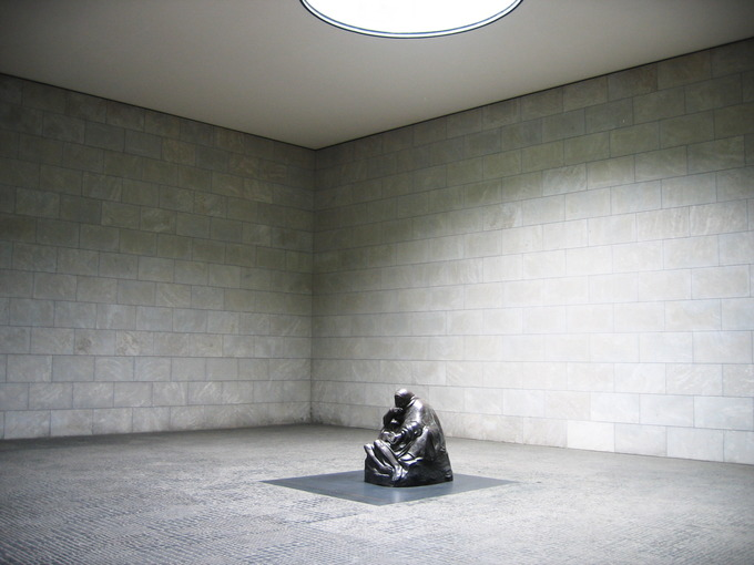 Photo of the sculpture depicting a mother cradling her dead son in a large, empty room.