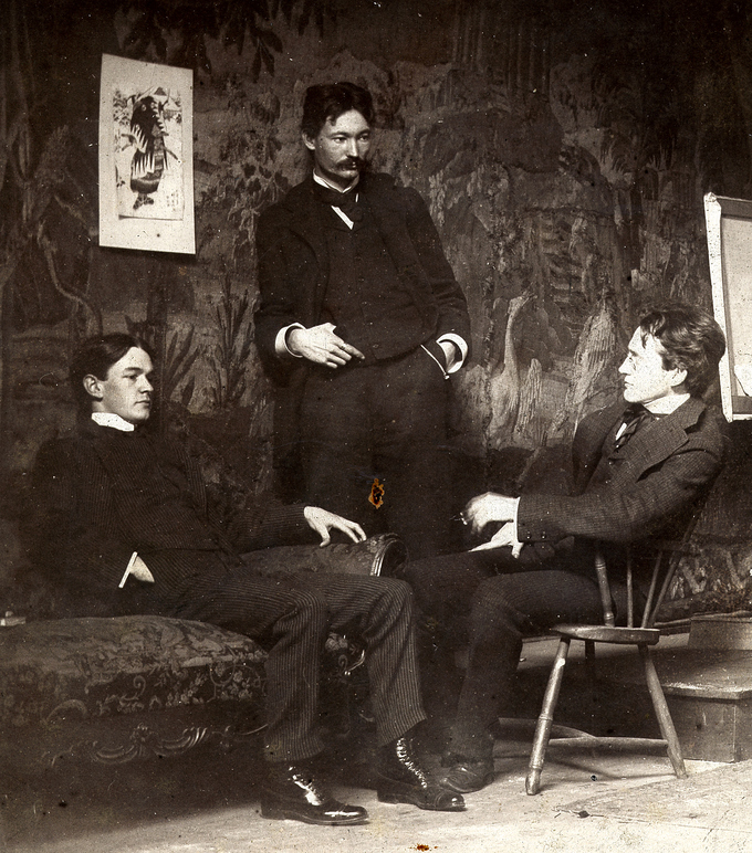 A black and white photo of the three artists at leisure with each other. Shinn and Sloan are seated, and Henri stands between them.