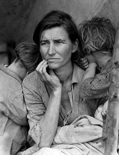 A sitting woman with a concerned expression holds a baby. Two children on either side of her hide their faces from the camera.