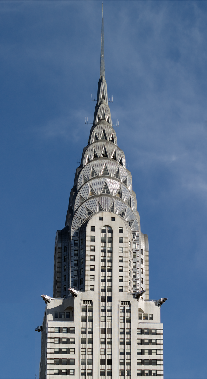 The spire is composed of seven radiating terraced arches, mounted up one behind another. The cladding is ribbed and riveted in a radiating sunburst pattern with many triangular vaulted windows.