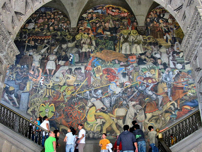 This current-day photo shows a mural in the main stairwell of the National Palace by Diego Rivera. The mural is a huge, colorful collection of indigenous images.