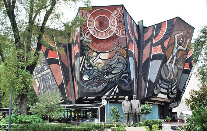 Picture of the exterior of the building. A statue of two men is in front of the building, and a colorful mural with several images covers the entire outside wall.