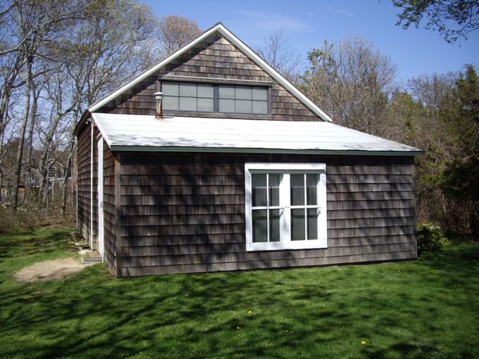 A photo of the exterior of the Pollock Barn. It is a plain, small house with dark shingles and white windows.