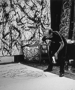 This black and white photo shows Jackson Pollock at work in his studio.