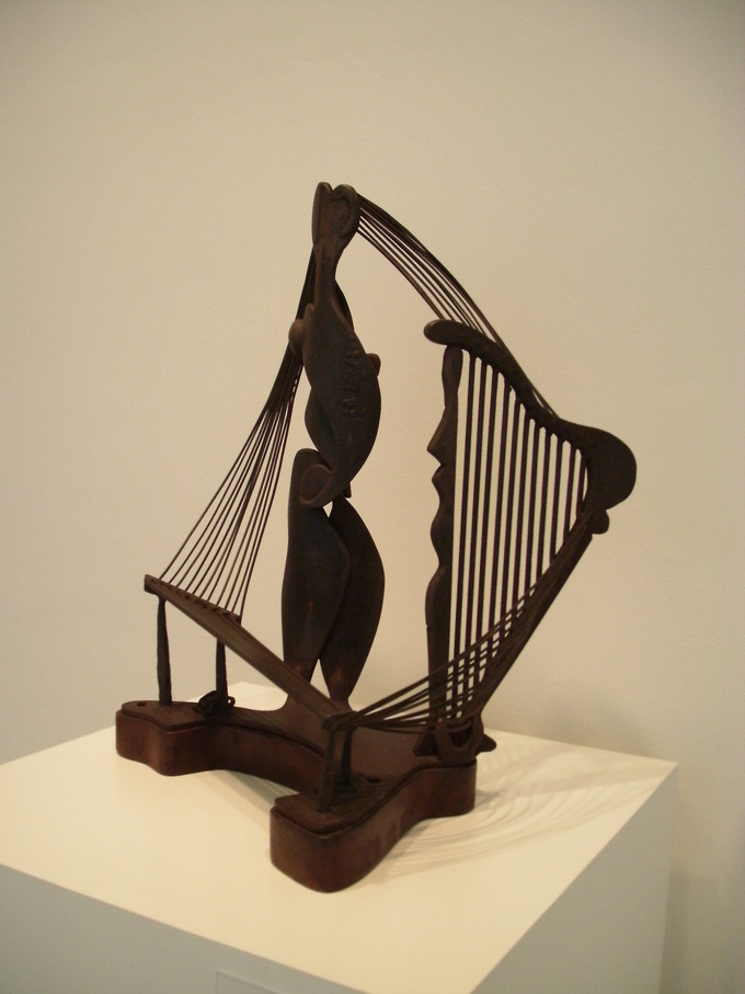 A wooden looking sculpture made up of abstract images. There is a central piece with string-like objects on either side.