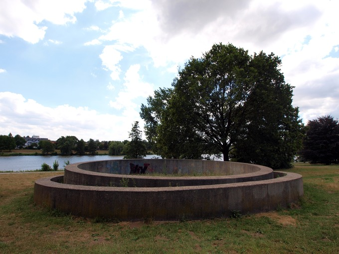 A concrete circle placed inside another concrete circle. Sculpture is outside in a field.